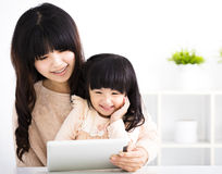 Happy mother and daughter using digital tablet Royalty Free Stock Photo