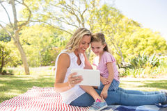 Happy mother and daughter using digital tablet in park Stock Photos