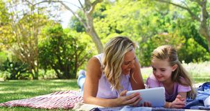 Happy mother and daughter using digital tablet in park 4k. Happy mother and daughter using digital tablet in park on a sunny day 4k stock footage
