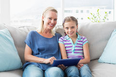 Happy mother and daughter using digital tablet on sofa Royalty Free Stock Image