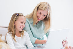 Happy mother and daughter using laptop Royalty Free Stock Photos