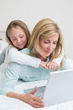 Happy mother and daughter using laptop Stock Photo