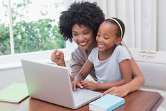 Happy mother and daughter using the laptop Stock Photo