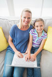 Happy mother and daughter using laptop on sofa Stock Photos