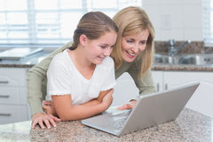 Happy mother and daughter using laptop together Royalty Free Stock Photos