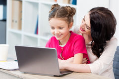 Happy mother and daughter using laptop at workplace Stock Images