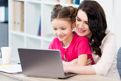 Happy mother and daughter using laptop at workplace Stock Photography