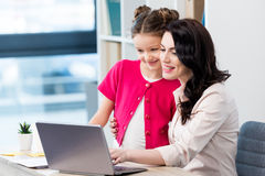 Happy mother and daughter using laptop at workplace Stock Image