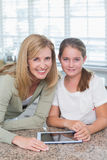 Happy mother and daughter using tablet pc together Stock Photography