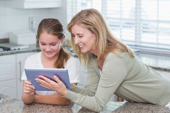 Happy mother and daughter using tablet pc together Stock Images
