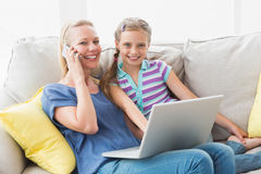 Happy mother and daughter using technologies on sofa Royalty Free Stock Image