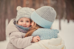 Happy mother and daughter on the walk in snowy winter Royalty Free Stock Photos