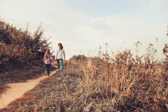 Happy mother and daughter on the walk on summer field. Family spending vacation outdoor Royalty Free Stock Image