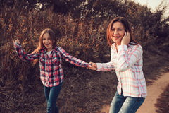 Happy mother and daughter on the walk on summer field. Family spending vacation outdoor Royalty Free Stock Photos