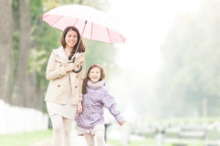 Happy mother and daughter walking in park. Royalty Free Stock Photos