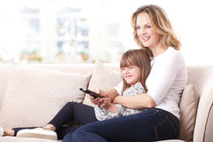 Happy mother and daughter watching tv Stock Photos