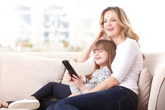 Happy mother and daughter watching tv Stock Photo