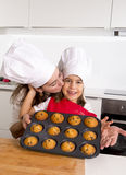 Happy mother with daughter wearing apron and cook hat presenting muffin set baking together at home kitchen Stock Photography