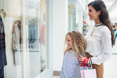 Happy mother and daughter window shopping in mall Stock Images