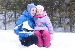 Happy mother and daughter in a winter park Stock Photo