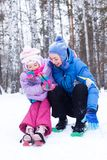 Happy mother and daughter in a winter park Stock Image
