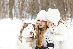 Happy mother with daughter in the winter park with huskies dog Royalty Free Stock Images
