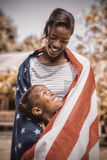 Happy mother and daughter wrapped in American flag at park Stock Photos