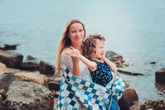 Happy mother and daughter wrapped in quilt blanket spending time together on the beach on summer vacation. Happy family traveling. Cozy mood Royalty Free Stock Photo