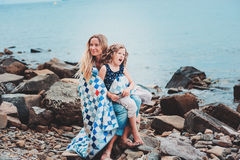 Happy mother and daughter wrapped in quilt blanket spending time together on the beach on summer vacation. Happy family traveling. Cozy mood Royalty Free Stock Image
