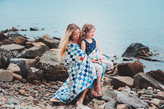 Happy mother and daughter wrapped in quilt blanket spending time together on the beach on summer vacation. Happy family traveling Royalty Free Stock Photography