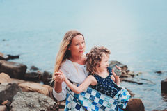 Happy mother and daughter wrapped in quilt blanket spending time together on the beach on summer vacation. Happy family traveling Royalty Free Stock Image