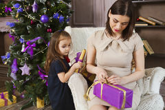 Happy mother with daughter wrapping Christmas gifts at home Stock Image