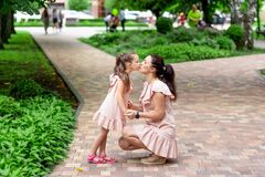 Happy mother and daughter 5-6 years old walk in the Park in the summer, mother kisses her daughter, the concept of a happy family
