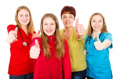 Happy mother with daughter and the young female doctors. Photo of happy mother with daughter and the young female doctors showing thumbs up Royalty Free Stock Photos
