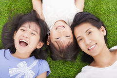 Happy mother and daughters lying on a meadow royalty free stock photography