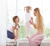 Happy mother and daughters playing in the bedroom Stock Photography