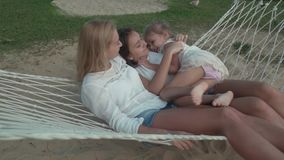 Happy mother with daughters rocking in hammock slow motion stock footage video stock video footage