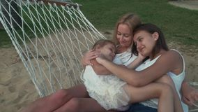 Happy mother with daughters rocking in hammock slow motion stock footage video stock footage video stock video