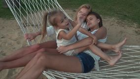 Happy mother with daughters rocking in hammock slow motion stock footage video stock footage video stock video footage