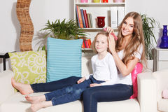 Happy mother doing daughter's hairdo Royalty Free Stock Image
