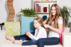 Happy mother doing daughter's hairdo Royalty Free Stock Photo