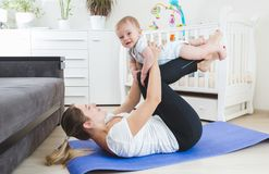 Happy young mother doing fitness exercises with her 9 months old baby boy. Happy mother doing fitness exercises with her 9 months old baby boy Royalty Free Stock Image