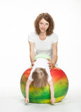 Happy mother doing sport exercises with little daughter. On a fitball Royalty Free Stock Photo