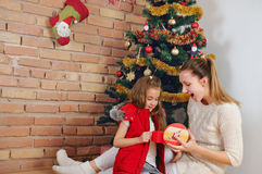 Happy mother and doughter having fun and open their presents for Royalty Free Stock Image
