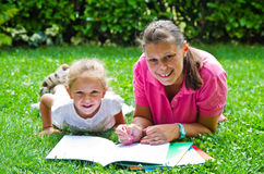 Happy mother drawing a book with baby girl Stock Photos