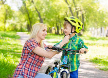 Happy mother dresses her son bicycle helmet Royalty Free Stock Photography