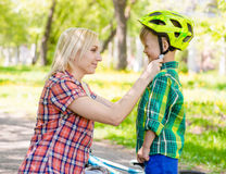 Happy mother dresses her son bicycle helmet Royalty Free Stock Images