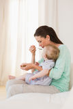 Happy mother eating with her baby boy Stock Image