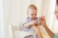 Happy mother eating with her baby boy Stock Photos
