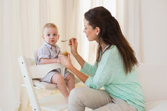 Happy mother eating with her baby boy Royalty Free Stock Images